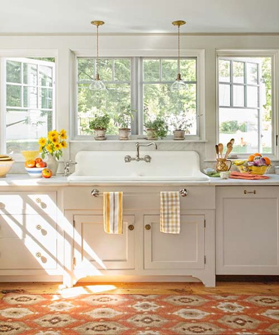 White kitchen with sunlight and open windows.