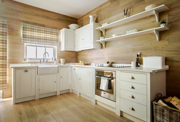 Wood panel kitchen with off-white painted cabinets.